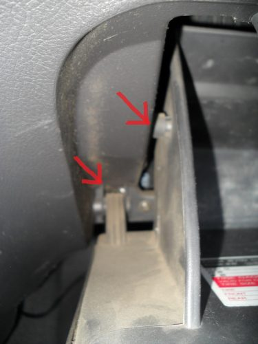 С помощью отвертки аккуратно поддеваем два стопора крышки бардачка