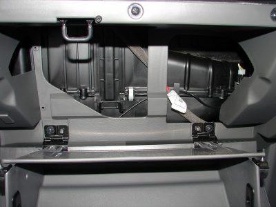 В центре бардачка расположена заглушка, которая фиксируется защелкивающим устройством с двумя фиксаторами. Сожмите фиксаторы, освободите заглушку и снимите.