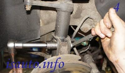 Зачистите места соединений деталей щеткой с металлической щетиной. Снимите болты, фиксирующие поворотный кулак и амортизационную стойку.